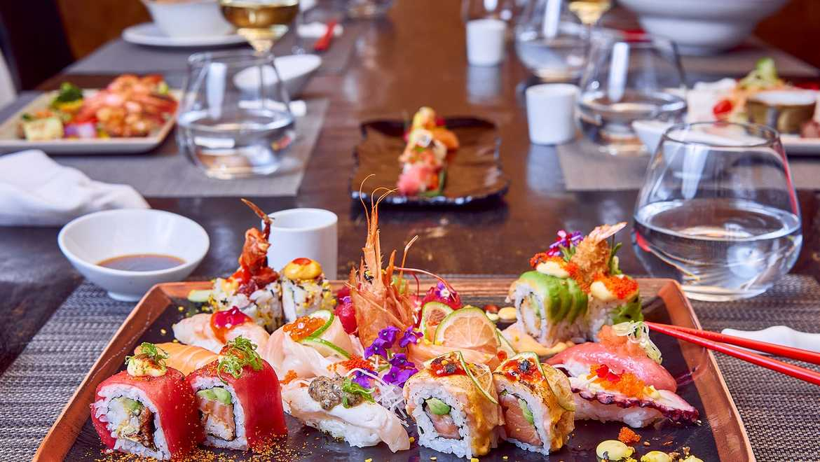 A plate of different types of sushi on a long wooden table.
