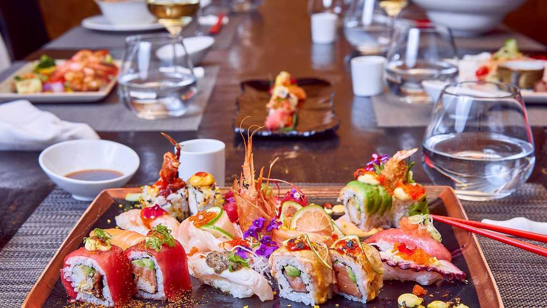 Un plato de diferentes tipos de sushi en una larga mesa de madera.